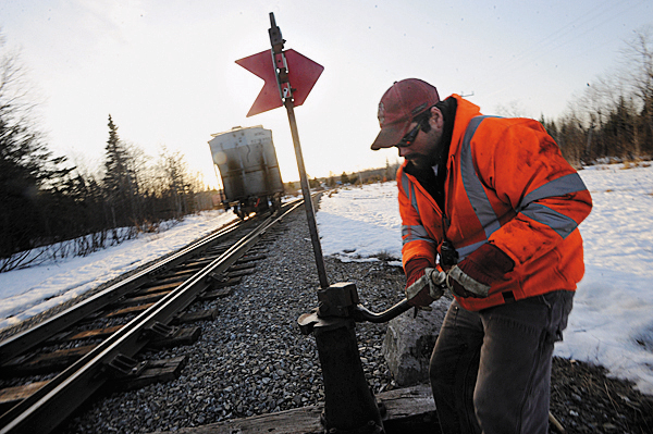 Just before sunset, conductor Jarrad Clark throws a switch on the Montreal, Maine and Atlantic railway so engineer Rick Cameron could return the train to the Squapan siding in Ashland from their bi-weekly Job 120 trip to Presque Isle Thursday, March 18, 2010.  BANGOR DAILY NEWS PHOTO BY JOHN CLARKE RUSS
