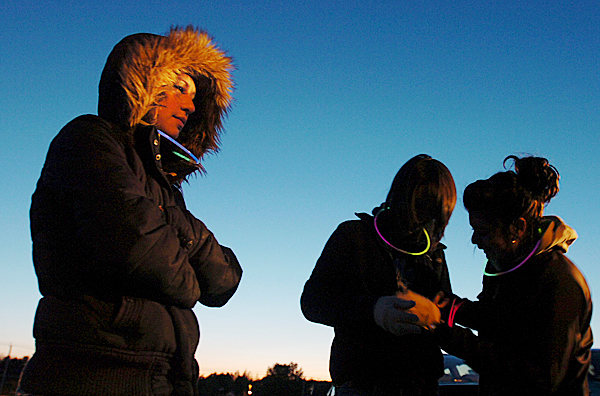 Danielle Lanler, left, bundles up against the cold as Moneia Arsenault, center, and Kate Leino, right, affix glow bands on each other before a memorial walk to remember Nate Clark of Hampden. The three Hampden Academy classmates were joined by a small group of Clark supporters as they planned their walk from St. Mathews Church on Western Ave. on Friday, March 26, 2010 to the bronze bronco at Hampden Academy and back.  BANGOR DAILY NEWS PHOTO BYKEVIN BENNETT