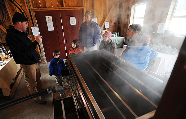 Lance Oliver, left, offers a first hand look and informatiion on how a maple syrup evaporator works to the Brown family of Castine on Sunday, March 28, 2010. Oliver operates the maple syrup production at Wentworth Hill Farms in Knox.  This is the first year the farm has offered maple syrup for sale to the public and has opened its doors during Maine Maple Sunday. Tours of the sugar bush were available to those that wanted to learn more. BANGOR DAILY NEWS PHOTO BY KEVIN BENNETT