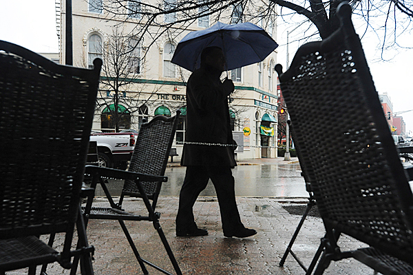 A pedestrian strolls along Hammond Street in Bangor as the steady rain continued throughTuesday, March 30, 2010. BANGOR DAILY NEWS PHOTO BY KEVIN BENNETT