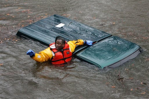 Yonkers, N.Y. firefighter Jerry Thompson checks for occupants of a submerged vehicle on a flooded section of the Bronx River Parkway in Bronxville, N.Y., Tuesday, March 30, 2010. The driver was already pulled to safety. (AP Photo/The Journal News, Frank Becerra Jr.) **MANDATORY CREDIT; NYC OUT, TV OUT, MAGS OUT, NO SALES**