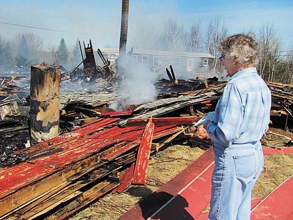 Judy McKenzie of Newport surveys the remains of the former Bar-L Ranch Friday. McKenzie, who used to own the property, was one of the first people to notice that it was on fire Thursday at about 9:30 p.m.  BANGOR DAILY NEWS PHOTO BY CHRISTOPHER COUSINS