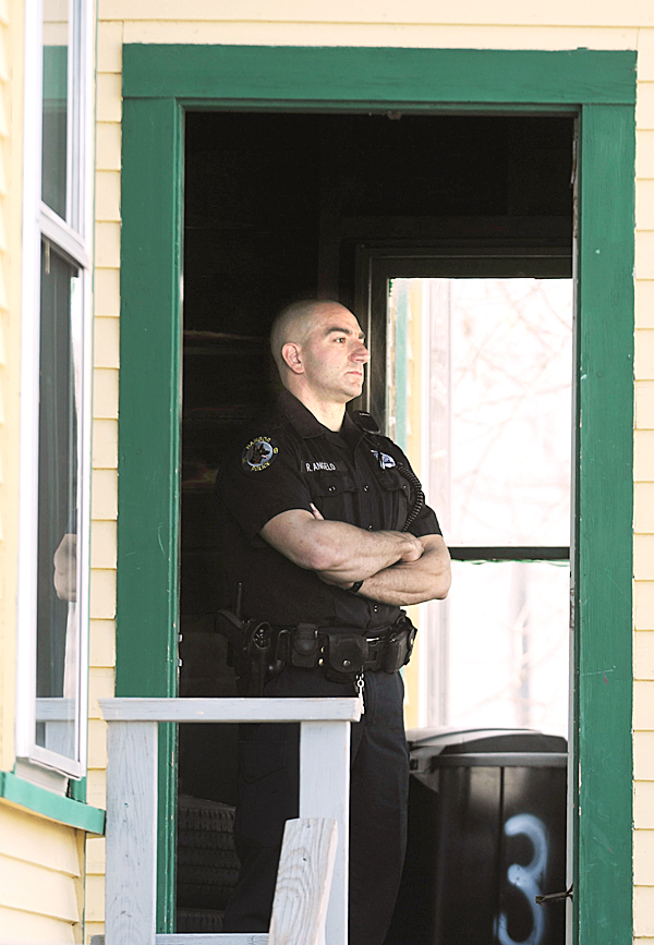 Bangor police Officer Rob Angelo stands watch in the entrance of 64 Ohio Street on Friday, April 2, 2010 as Bangor police investigated an beating at that location.  A 53- year-old man, whose name was not released, was taken to Eastern Maine Medical Center for treatment of blunt force trauma injuries.  Police have not arrested a suspect in the assault.   BANGOR DAILY NEWS PHOTO BY KEVIN BENNETT