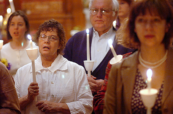Karen and Chris Maas of Dover-Foxcroft (from left) and Olga Dobbins of Levant (right) participate in a midnight mass in celebration of Holy Pascha or Easter at St. George Orthodox Church in Bangor early Sunday morning, April 4, 2010. BANGOR DAILY NEWS PHOTO BY BRIDGET BROWN