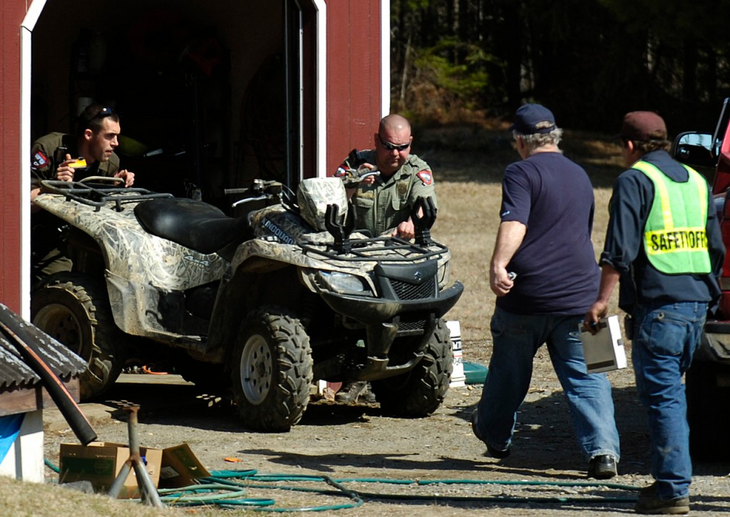 Game Wardens Eric Rudolph, left and Rick Ouellette, center, push a Suzuki King Quad out of a shed for inspection on Monday, April 5, 2010 as Alton fire fighter Maynard Trafton and Lt. Brian Ouelette move in to help. The ATV was crashed by a 15 year-old male from Maryland about 1000 feet this location. The juvenile was not wearing a helmet and was transported to EMMC in Bangor.  (Bangor Daily News/Kevin Bennett)