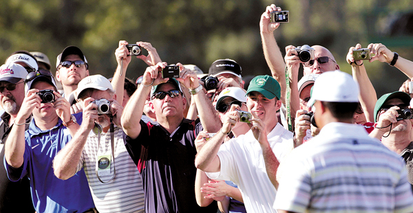 Spectators take photos of Tiger Woods during his practice round for the Masters golf tournament in Augusta, Ga., Monday, April 5, 2010. The tournament begins Thursday, April, 8. (AP Photo/David J. Phillip)