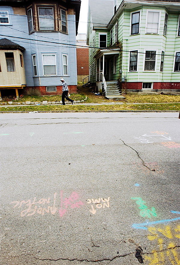 A pedestrian goes past houses on Sanford Street on Monday, April 5, 2010. The Bangor Y has purchased these houses along with several others and will demolish them to make way for an expansion of the exisiting Y building. BANGOR DAILY NEWS PHOTO BY KEVIN BENNETT
