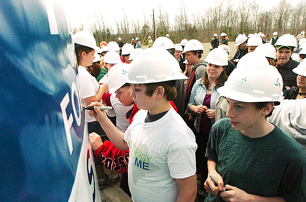 Students from  East Grand High School sign a banner during a ribbon cutting celebration at First Wind's Stetson II wind farm, which added 17 new wind turbines to their wind power project near Danforth, Tuesday, April 6, 2010. (Bangor Daily News/Kevin Bennett)