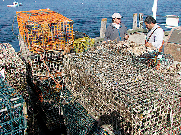 Gulf of Maine Lobster Foundation Project Manager Laura Ludwig, left, talks Wednesday to Sorrento fishermen James West as they stand next to a pile of recovered lobster traps on the Bar Harbor Town Pier. West was one of a handful of Mount Desert Island area fishermen who help the foundation recover lobster traps around the island on Tuesday and Wednesday. BANGOR DAILY NEWS PHOTO BY BILL TROTTER