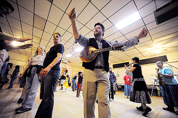 Belfast Flying Shoes conductor and mandolin player Thomas Fowler of Belfast conducts the All Comers Band as his sister Chrissy Fowler (cq), right,  gives folks instructions for the next dance during the contradance at American Legion Post 43 Friday night, April 2, 2010. On the left is participant Gina Krummel of China, ME. BANGOR DAILY NEWS PHOTO BY JOHN CLARKE RUSS