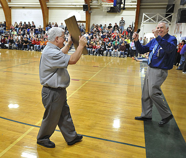 Penquis Valley Community High School principal Clay Savage, right, reacts as teacher Walter Oakes lifts aloft his dedication plaque at a school assembly Friday, April 9, 2010, in Milo, Maine.   BANGOR DAILY NEWS PHOTO BY MICHAEL C. YORK