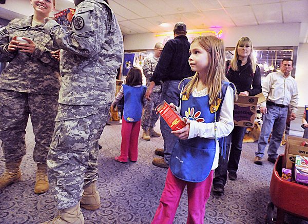 Suzanne Webb wanders around the crowd of servicemen and servicewomen enroute to deployment in the middle east trying to give away some Girlscout cookies as a gift, Friday, April 9, 2010. Troop 109, Hampden, collected enough donations to offer 500 boxes as gifts to troops passing through Bangor International Airport.   BANGOR DAILY NEWS PHOTO BY MICHAEL C. YORK