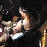 "Ed ""Wiz"" Dumont of Wiz Tattoos in Brewer works on Angella Moser of Jonesboro at the Down East Tattoo Show in Hermon on Saturday, April 10, 2010. ""He's been tattooing me for the last 20 years,"" said Moser of Dumont. The theme of this year's show was ""Invasion of Pirates"". BANGOR DAILY NEWS PHOTO BY BRIDGET BROWN"