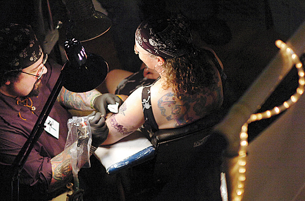 Ed &quotWiz&quot Dumont of Wiz Tattoos in Brewer works on Angella Moser of Jonesboro at the Down East Tattoo Show in Hermon on Saturday, April 10, 2010. &quotHe's been tattooing me for the last 20 years,&quot said Moser of Dumont. The theme of this year's show was &quotInvasion of Pirates&quot. BANGOR DAILY NEWS PHOTO BY BRIDGET BROWN