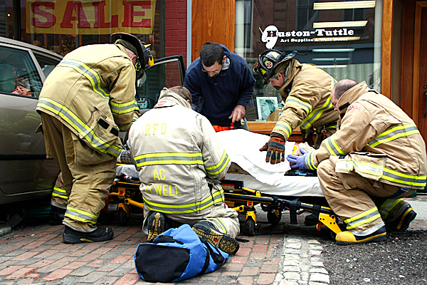 Emergency workers attend to the driver of a car that crashed into The 