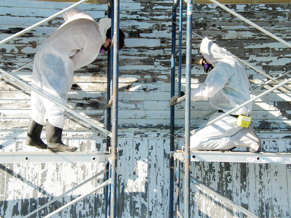 Wearing white suits and gear, workers from County Abatement Inc. scrape lead paint this week from the historic Station 98 building, thhe former railway station in Machias.  (BANGOR DAILY NEWS PHOTO BY KATHERINE CASSIDY)
