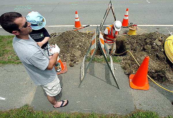 Homeowner Mark Blaine (left) and his son Ethan watch Bangor Gas employee Chris Chambers as he installs natural gas piping under Washington Street in Brewer to connect to Blaine's home. &quotIt's a matter of being able to heat your house for the winter,&quot Blaine said when asked why he's incurring the added expense of converting from oil heat to natural gas.  (BANGOR DAILY NEWS PHOTO BY KEVIN BENNETT)  CAPTION  Home owner Mark Blaine, left, and his son Ethan watch Bangor Gas employee Chris Chambers, right, as he installs natural gas piping under Washington Street in Brewer to connect to Blaine's home.  &quotIt's a matter of being able to heat your house for the winter,&quot explained Blaine when asked why he's incurring the added expense of converting from oil heat to natural gas. (Bangor Daily News/Kevin Bennett)