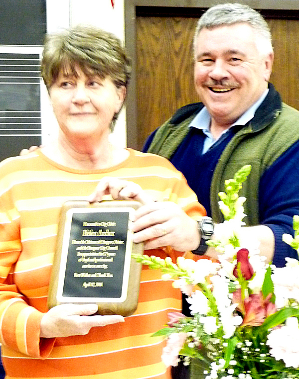 PHOTO GOES WITH MACK STORY ECOUNCIL Helen Archer accepts a plaque and flowers from Robert Peacock, chairman of the city council, at Monday night's Eastport council meeting. Archer will retire on April 30 after 37 years as Eastport's city clerk. (Bangor Daily News phot by Sharon Mack)