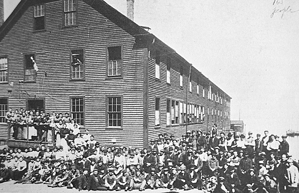 165 sardine cannery workers pose for a photo outside the Grady Sardine Factory on the Eastport waterfront, circa 1890.   PHOTO COURTESY OF BORDER HISTORICAL SOCIETY