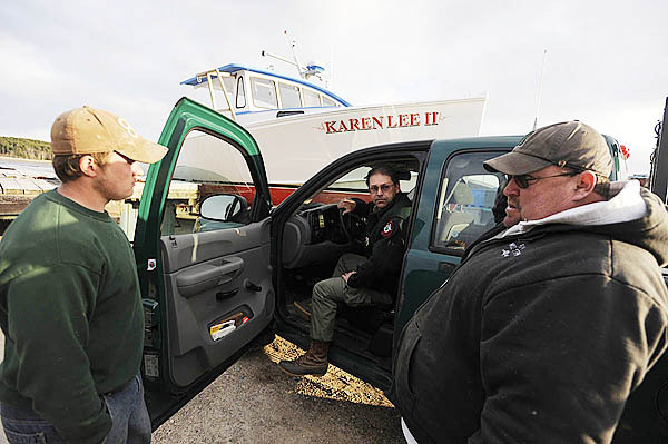 Local fishermen Dicky Wallace of Milbridge (left) and Alfred Haycock (right) of Milbridge talk with Marine Patrol Officer Royce Eaton (center) after returning to Chipman's Point in Steuben around 6 p.m. They spent most of the day with other local fishermen, Maine Marine Patrol, Maine Warden Service, State Police and Coast Guard personnel searching for two missing brothers who failed to arrive by boat Wednesday morning at Bois Bubert Island. By late afternoon Wednesday one body had been recovered. (Bangor Daily News/John Clarke Russ)