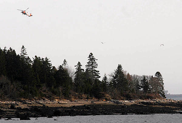 A Coast Guard helicopter hovers over the southeast portion of Bois Bubert Island around 6 p.m. as part of Wednesday's search for a second missing boater. By late afternoon Wednesday one body had been recovered. (Bangor Daily News/John Clarke Russ)