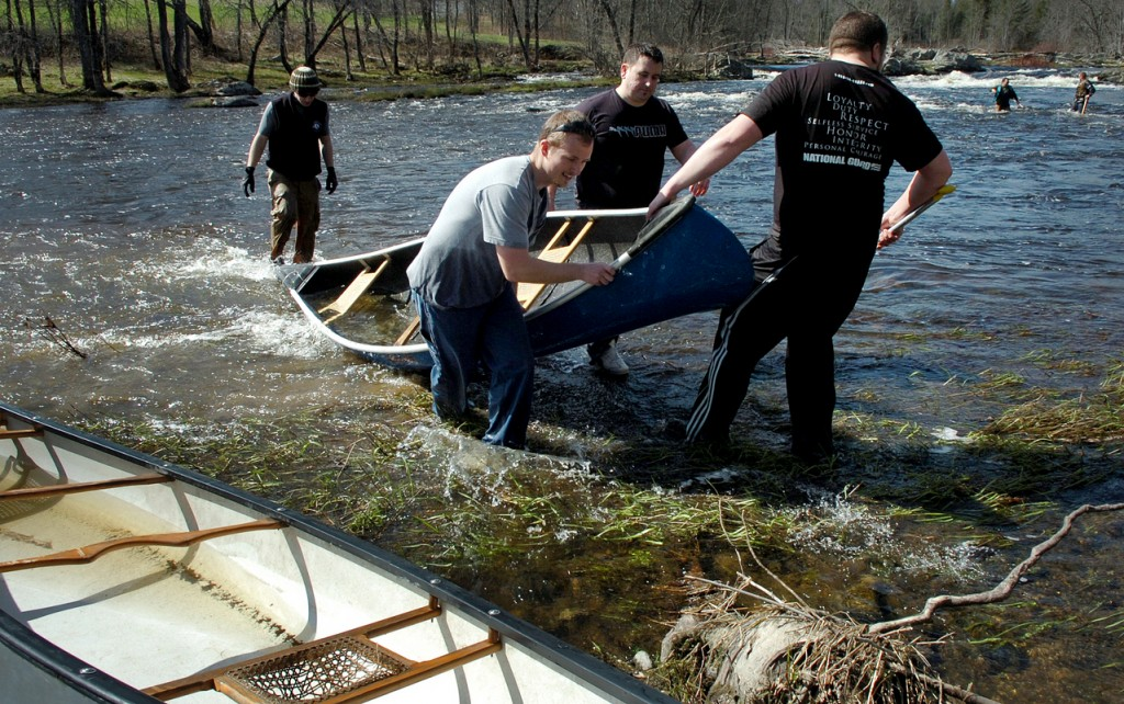 Benjamin Bustard (from left), Buddy Eckman, Jim Funari and Nick Bemis help drag out the canoe lost by Dave Dube and Kirk Winters when they capsized at Six Mile Falls on the Kenduskeag Stream on Wednesday afternoon, April 14, 2010. The three pairs, who are all members of The Rock Church in Bangor, will be participating in Saturday's race for the first time to raise money for First Step Pregnancy Resource Center in Bangor. &quotIt's cold. My body's tingling,&quot said Funari of the water after he and his partner took a spill. (Bangor Daily News/Bridget Brown)