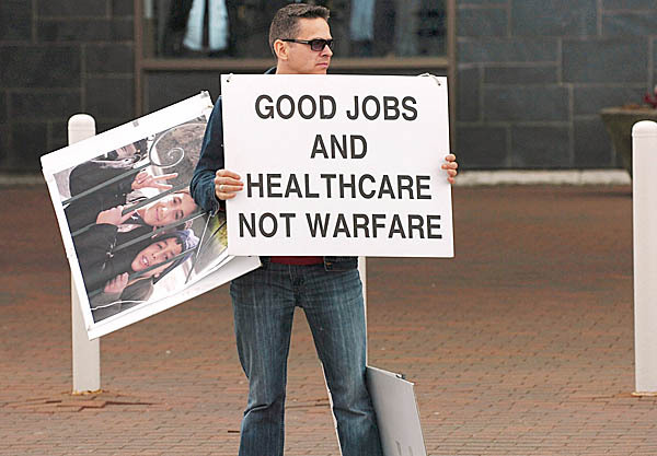 Blaine Shaw of Veazie demonstrates across Harlow Street from a tea party rally in downtown Bangor on Thursday, April 15, 2010.  BANGOR DAILY NEWS PHOTO BY BRIDGET BROWN