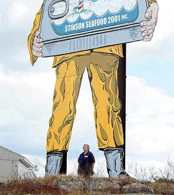 An employee of Stinson Seafood in Prospect Harbor poses for a picture at the large sign in the front of the cannery Thursday, April 15, 2010.   About 128 people will lose their jobs, as owner Bumblebee Foods decided to shut down the plant. The sardine cannery is the last one to operate in the U.S. and is turning out the last cans of sardines this week after 104 years in operation. (Bangor Daily News/Gabor Degre)