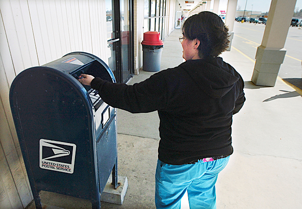 Danielle Subjoc of Kenduskeag drops mail into a post office box at the Broadway Shopping Center on Tuesday, April 13, 2010. The new temporary home of the Bangor post office will be located at the Broadway Shopping Center until arrangements are finalized on the former district court location on Hammond Street. BANGOR DAILY NEWS PHOTO BY KEVIN BENNETT