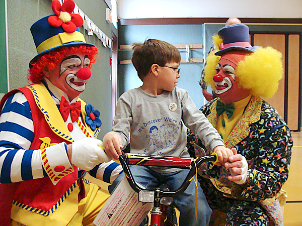Anah Temple clowns Ducky, left, and Gizmo, right, steady Milo Elementary School pupil Benjamin Bouley's new bicycle Friday as he tried it out for size. Bouley was one of several children in the Milo, Brownville and Lagrange areas to get a new bicycle provided by the local Masonic lodges through their Bikes for Books program.   BANGOR DAILY NEWS PHOTO BY DIANA BOWLEY