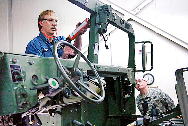 Mechanical technician Wayne Wasson prepares to install a windshield on a Humvee as Major General Raymond Carpenter, Director of the Army National Guard (right), looks on at Maine Military Authority in Limestone on Friday, April 16, 2010. Carpenter joined Maine Sen. Susan Collins and others on Friday's tour &quotto explore alternative options for work at the facility,&quot according to Collins. BANGOR DAILY NEWS PHOTO BY BRIDGET BROWN