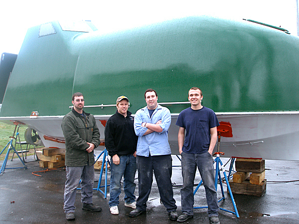 Student researchers Travis Wallace, a graduate student at the University of Maine, and Maine Maritime Academy seniors Christian Beauregard, Chris Wallace and Andrew Blackman, stand in front of the lifeboat they are converting so that they can capture waste heat from the boat's diesel engine and convert it to electrical power. They hope to complete the conversion in time to test it on the water before the end  of this month.  BANGOR DAILY NEWS PHOOT BY RICH HEWITT