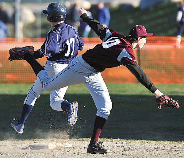 WA's Toby Woods ,(10), gets pulled off the bag by an errant throw allowing Calais' Jesse Clark,(17), to reach safely in the  fourth inning of the game in East Machias, Friday, April 16, 2010.  BANGOR DAILY NEWS PHOTO BY MICHAEL C. YORK