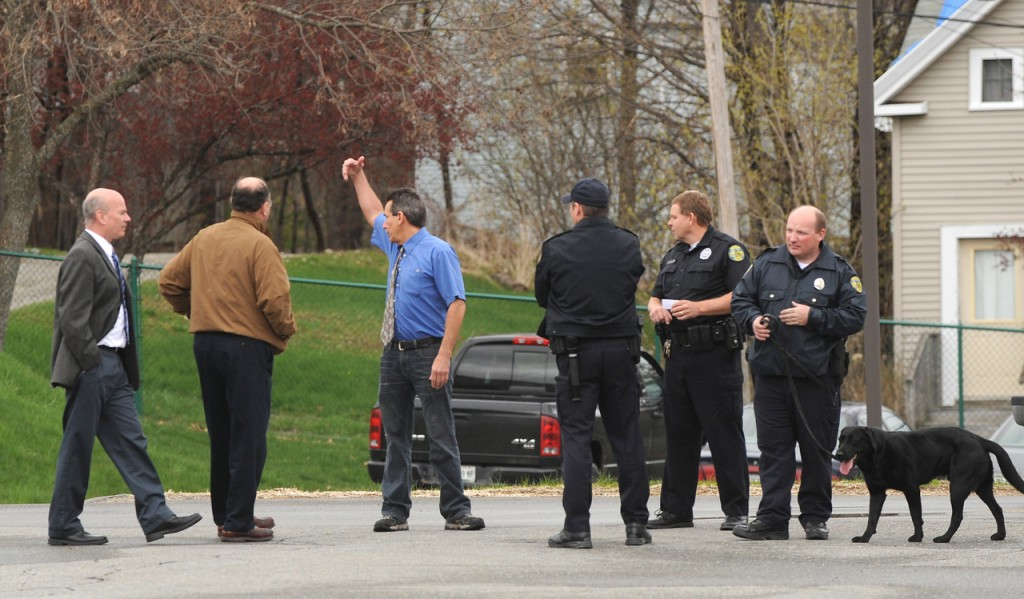 Bangor Daily News managers signal to the emloyees that it is safe to enter the building after police checked it following a bomb threat that was called in for the Main Street location. (Bangor Daily News/Gabor Degre)
