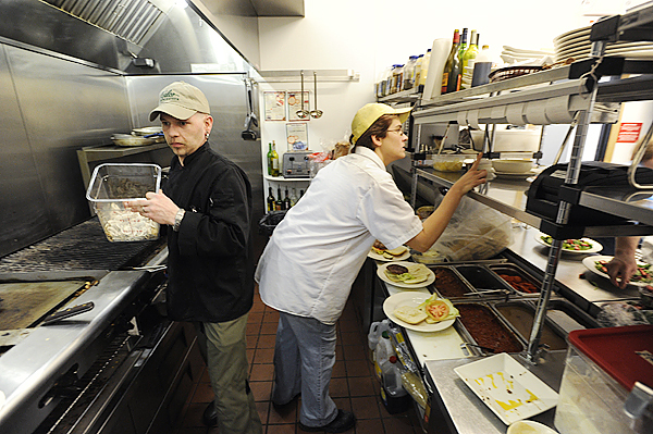 (BANGOR DAILY NEWS PHOTO BY JOHN CLARKE RUSS)  CAPTION  Head Chef Josh Stevens, left,  of Millinocket gets ready to prepare a dish as cook Aimee Stewart (cq) of Millinocket looks over an order at Pelletier Loggers Family Restaurant Bar and Grill during lunchtime Tuesday, April 13, 2010. The Millinocket restaurant opened in March of this year and has drawn large crowds, including fans of the &quotAmerican Loggers&quot television show which features members of the Pelletier family. (Bangor Daily News/John Clarke Russ)