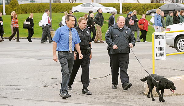 Bangor Police officers and Bangor Daily News Director of Production Charlie Villard (left) walk around the newspaper's office on Main Steet after checking the building following a bomb threat. The employees waited outside for about 45 minutes. (Bangor Daily News/Gabor Degre)