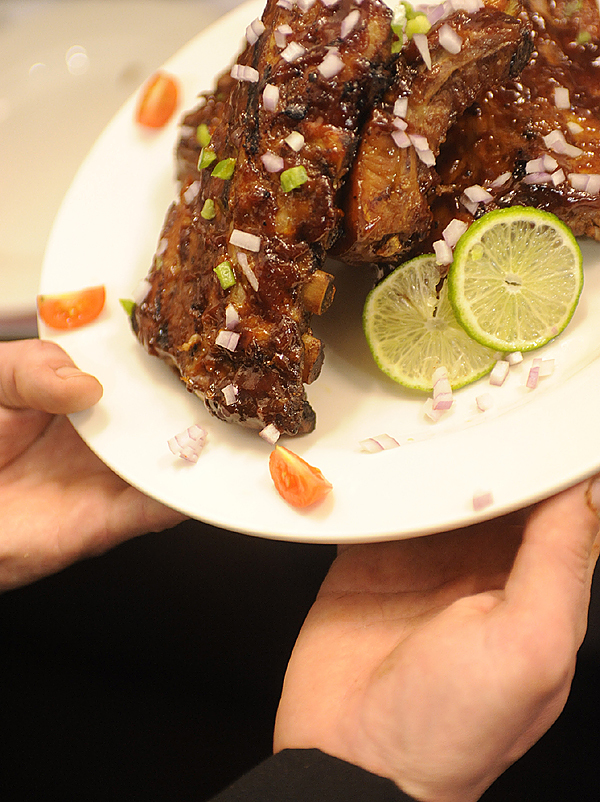 (BANGOR DAILY NEWS PHOTO BY JOHN CLARKE RUSS)  CAPTION  During lunchtime Tuesday, head chef  Josh Stevens of Millinocket shows off the &quotPiledown&quot (tender ribs served with a secret recipe BBQ sauce and coloful garnish). The Millinocket restaurant opened in March of this year and has drawn large crowds, including fans of the &quotAmerican Loggers&quot television show which features members of the Pelletier family. (Bangor Daily News/John Clarke Russ)