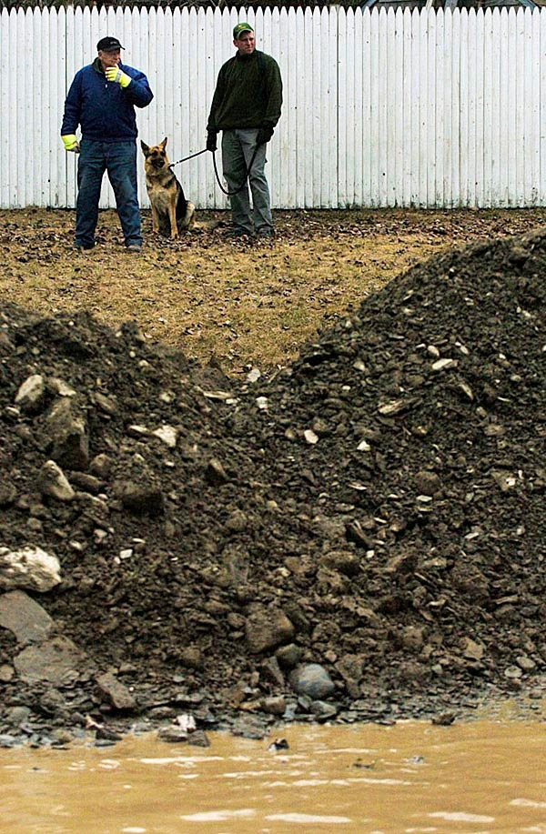 Donald Hodgson (left), his son, Donald, and their German shepherd, Rain, watch muddy floodwater travel past a dirt berm on West Main Street in Fort Kent near the Fish River Bridge. The Fort Kent Public Works Department constructed the berm to divert floodwater.  BANGOR DAILY NEWS FILE PHOTO BY JOHN CLARKE RUSS
