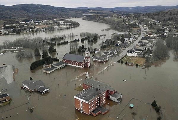 Part of Fort Kent, with St. Louis Catholic Church in the center, was flooded Wednesday when the Fish River spilled over its banks near the confluence with the St. John River (top left).  BANGOR DAILY NEWS FILE PHOTO BY JOHN CLARKE RUSS