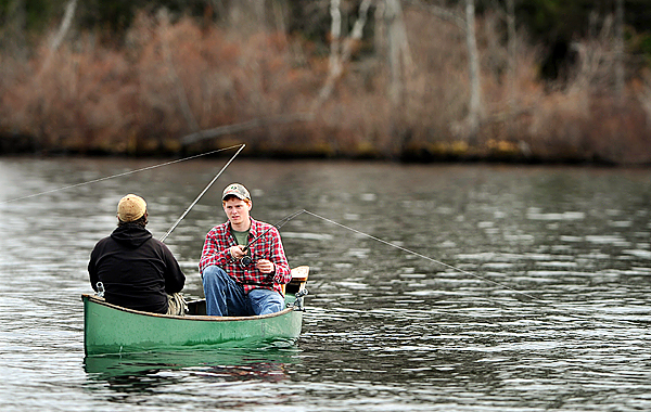 Taking advantage of their school vacation, Eliot Lamb, left, and Dylan Thomas, right, both of Orono, fish in the waters of Pushaw lake on Tuesday, April 20, 2010. Thomas said he had already landed a good-sized bass. (Bangor Daily News/Kevin Bennett)