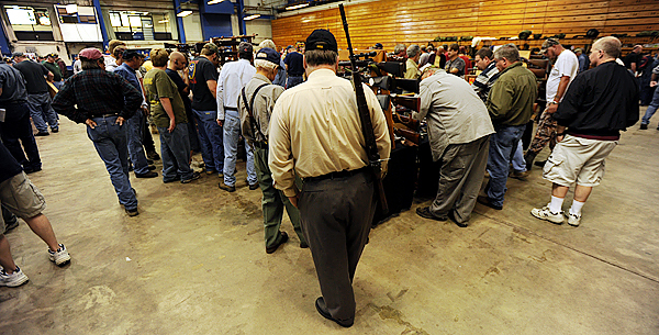 Most vendor tables at the Bangor Gun Show had gun enthusiasts two-and theree-deep waiting to see new or used firearms or accessories offered for sale or trade during the show at the Bangor Auditorium in September.  (BANGOR DAILY NEWS PHOTO BY KEVIN BENNETT) otis  CAPTION  Most vendors tables at the Bangor Gun Show had gun enthusiast  2-3 deep waiting to see new or used guns or accessories being offered for sale or trade during the 2009 Bangor Gun Show at the Bangor Auditorium on Saturday, September 12, 2009. (Bangor Daily News/Kevin Bennett)