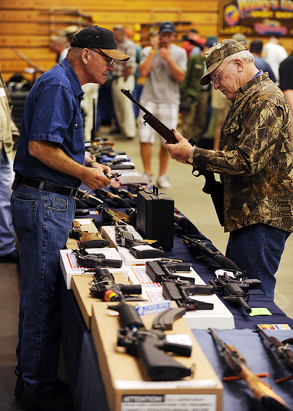 CAPTION Ivan Smith, right, of Lincoln, inspects a 100 Winchester 308 cal. deer hunting rifle  being offered for sale by Sidney Strom, left,  of Burgess Gun Sales of Bath during the Bangor Gun Show on Saturday, September 12, 2009. Smith said his deer and grouse hunting is &quot just a pastime&quot. (Bangor Daily News/Kevin Bennett)  (WEB EDITION PHOTO)