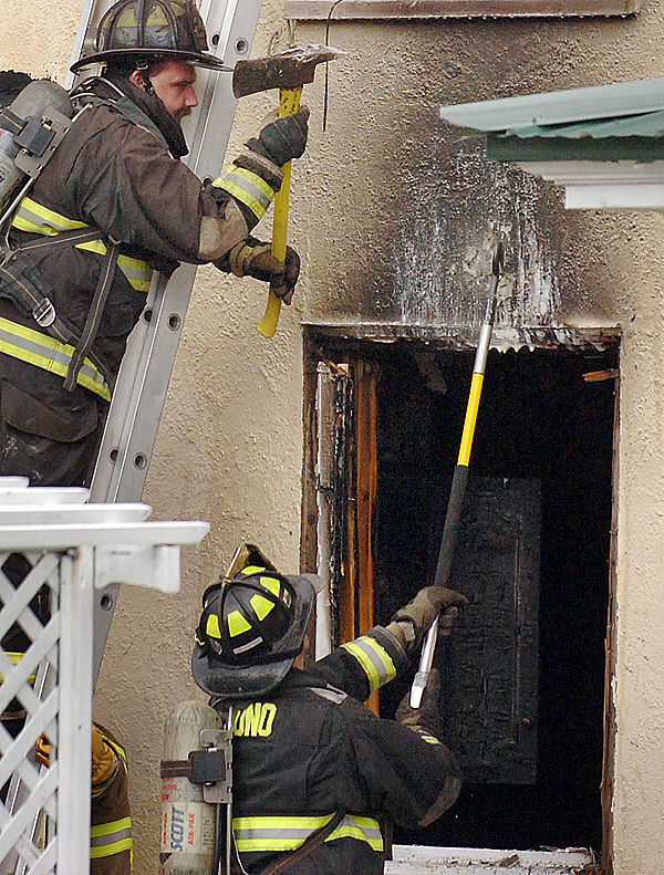 Firefighters work at the scene of a fire at the Stucco Lodge in Veazie on Wednesday evening, April 21, 2010. One woman at the residence received minor burns to her hand from the fire, but no one else was injured. (Bangor Daily News/Bridget Brown)