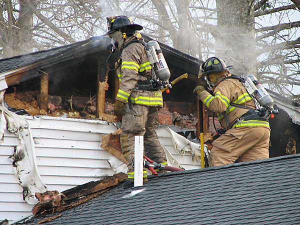 Firefighters stand on the roof of an Ellsworth hair salon on Wednesday as they work to extinguish a fire that broke out in an attached apartment. Ellsworth fire Chief Jon Marshall said no one was home at the time and there were no injuries. The cause of the fire had not been determined as of Wednesday evening. BANGOR DAILY NEWS PHOTO BY BILL TROTTER