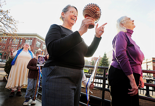 Left to right: Rev. Hazel Littlefield , Aksel Sander, 8 of Bangor, Rev. Joyce Elaine, Rev. Jan Silbury of Bangor with the Temple of the Feminine Divine invoke and devoke the North after pouring blessed water into the Kensduskeag Street in downtown Bangor. The ritual was part of their Earth Day celebration at sunset Thursday.  BANGOR DAILY NEWS PHOTO BY JOHN CLARKE RUSS