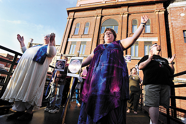 Rev. Deanna Partridge (center) of the Temple of the Feminine Divine invokes and devokes the South after she and other participants faced the other compass directions after pouring blessed water into the Kensduskeag Street in downtown Bangor. The ritual was part of their Earth Day celebration at sunset Thursday. Immediately next to Rev. Partridge was Rev. Hazel Littlefield (on left) of Jackson and Merlin Littlefield, right, (Hazel Littlefield's son) of Bangor. BANGOR DAILY NEWS PHOTO BY JOHN CLARKE RUSS