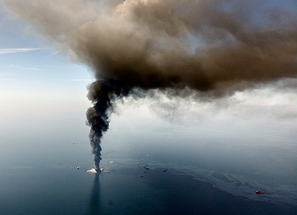 In this aerial photo taken Wednesday, April 21, 2010 in the Gulf of Mexico, more than 50 miles southeast of Venice on Louisiana's tip, an oil slick is seen as the Deepwater Horizon oil rig burns.  AP PHOTO BY GERALD HERBERT