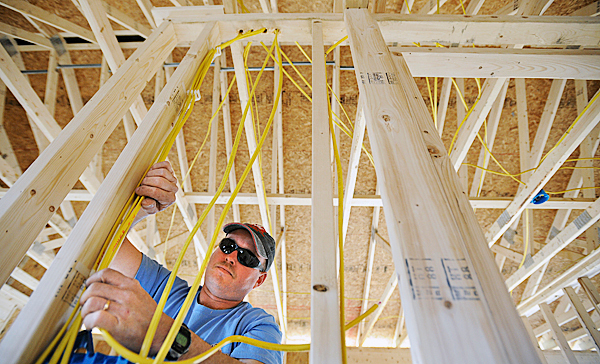 Andrew Dunn, an electrician with Woods of Maine, Inc., works on the wiring of a new home in new development in Bangor, Tuesday,pril 20, 2010.  Owner Mike Wood said that his company builds about 25-30 houses each year.  BANGOR AILY NEWS PHOTO BY GABOR DEGRE