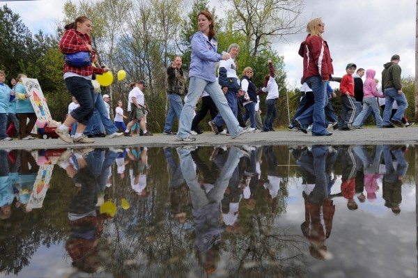 Some of the several hundred participants walk past a rain puddle which caught their reflection during Sunday afternoon's Walk for Autism at University College of Bangor. The event, one of several across the state on Sunday, was organized by the Autism Society of Maine to raise money for their children summer camp, family retreat weekend, an autism information specialist program and other needs. (Bangor Daily News/John Clarke Russ)