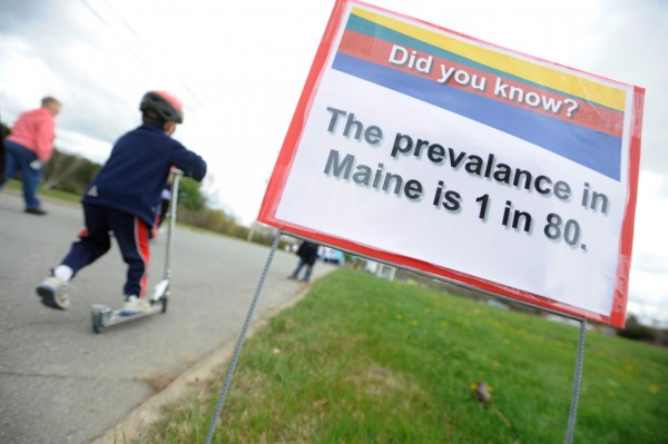 A child scootered past an information sign regarding autism in Maine during Sunday afternoon's Walk for Autism at University College of Bangor.  The event, one of several across the state on Sunday, was organized by the Autism Society of Maine to raise money for their childrens summer camp, family retreat weekend, an autism information specialist program and other needs. (Bangor Daily News/John Clarke Russ)